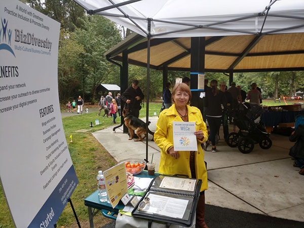 ESL Culture Coach Larissa Chuprina shows Welcome Eastside Center Ad in front of BizDiversity display at Welcome to Juanita 2018 at Edith Moulton Park in Kirkland, WA on September 15, 2018